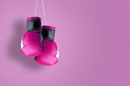 Roze hangende bokshandschoenen die tegen een roze achtergrond hangen. Lege kopie ruimte voor de tekst van de uitgever.