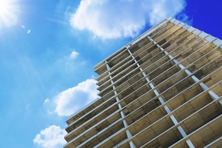 Bekistingsstructuur van een high-rise gebouw tegen een bewolkte blauwe hemel. Lege kopie ruimte voor de tekst van de uitgever.