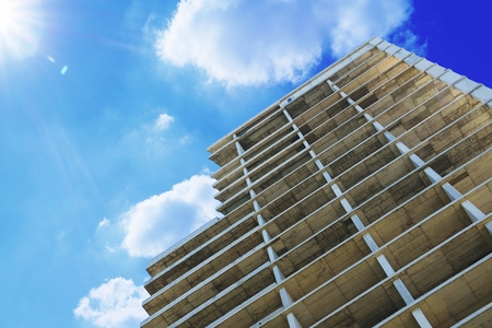Formwork structure of a high-rise building against a cloudy blue sky. Empty copy space for Publisher's text. Banque d'images