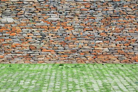 Natuurlijke stedelijke achtergrond. Stenen muur en geplaveide vloer met wat gras.