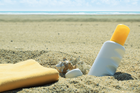 Sunscreen tube on the sand next to the beach. Empty copy space for Publisher's text. Banque d'images