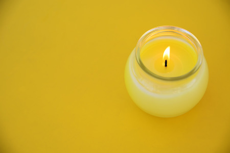 Yellow minimalist centerpiece with a citronella candle in a glass. Empty copy space for Publisher's text. Banque d'images