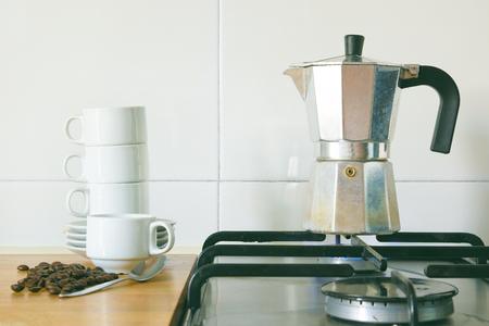 Een kopje koffie bereiden met een ketel op een brander in een rustieke keuken, naast een stapel kopjes en wat granen. Lege kopie ruimte voor de tekst van de uitgever. Stockfoto