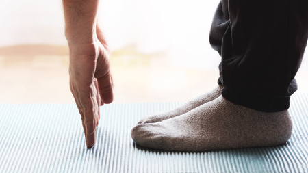 Adult person doing some yoga and meditation exercises on a mat in a class. Empty copy space for Publisher's text. Banque d'images