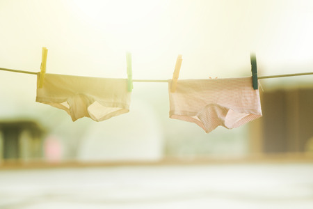 Two pants of twin babies hanging on a cord of a terrace in a peaceful village. Empty copy space for Publisher's text.