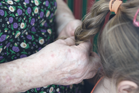 Grandmother hairdressing hand making a pigtail to her granddaughter. Family scene and generation concept.