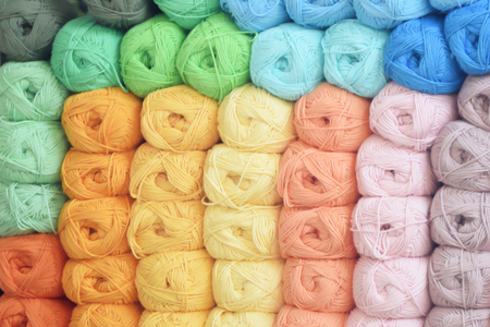 Some colorful balls of wool on a shelf of a new business shop. Colored background. Banque d'images