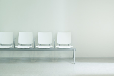 Waiting hall chairs forming a row against a white wall background. Empty copy space for Publisher's text. Banque d'images