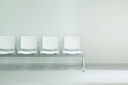 Wachtzaalstoelen die een rij vormen tegen een witte muurachtergrond. Lege kopie ruimte voor de tekst van de uitgever.