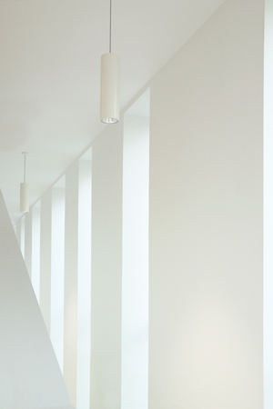 Architecture detail in a white interior. Vanishing point and some windows with natural light. Empty copy space for Publisher's text.
