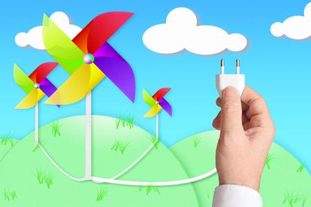 Een hand met een stekker aangesloten op een windmolen. Hernieuwbare energieconcept.