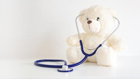 Urso de pelúcia com um estetoscópio. Cuidados de saúde pediatra para crianças. Espaço de cópia vazia para o texto do Publisher.