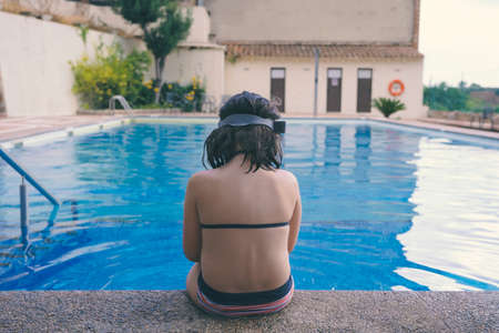 Sad girl sitting lonely at the edge of the pool. End of the summer and post-holiday depression.