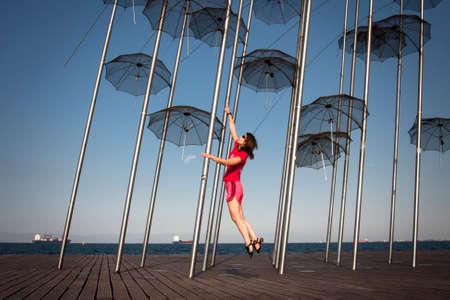 Girl jumping behind an umbrella