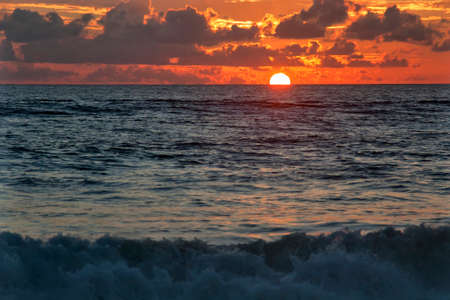 Sunset over the sea and the waves off the coast