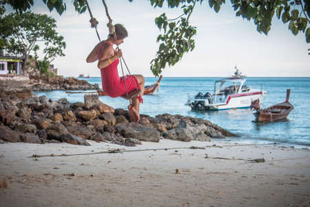 Girl on a swing by the sea