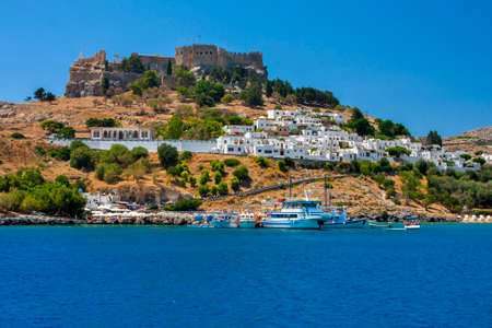 The ancient walled city stands on a high cliff on the shore of the blue sea