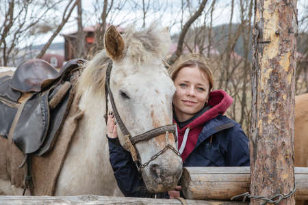 A beautiful girl stands with a horse. Friendship between a girl and a horse. Portraits of a girl and a horse. Pleasant and joyful emotions.
