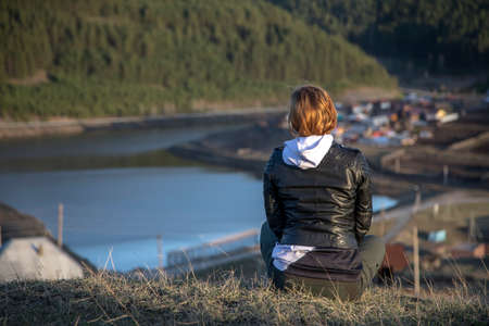 A beautiful girl sits on a mountain and looks into the distance. Girl's back. Beautiful landscape. Mountains and river. Evening sunset light. Stock Photo