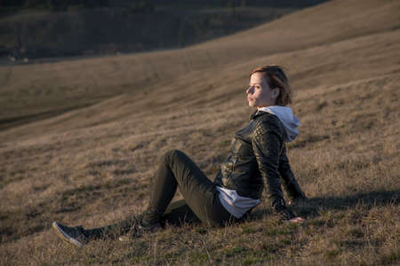 A beautiful girl sits on a mountainside and looks. Rural landscape. Beautiful nature. Sunny evening.