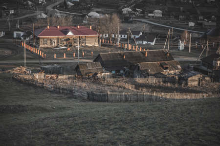 Beautiful Russian village at sunset. Nature, fields, mountains and hills. Warm evening. Colorful sunset light.
