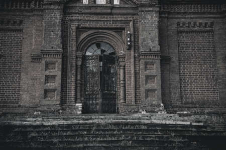 An old beautiful and scary abandoned church. Brick walls. Gloomy gothic atmosphere. Evening light. Stock Photo