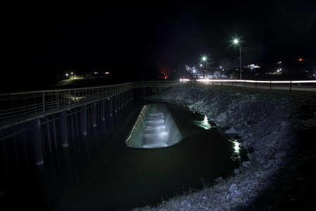 Small dam at night. Rural landscape. Lanterns and the road.