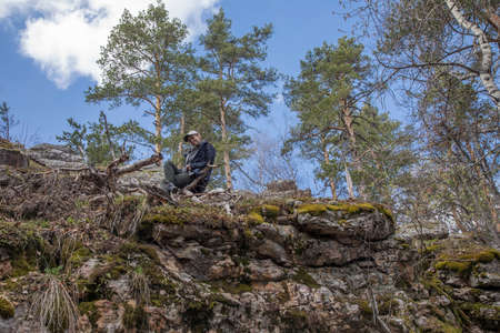 A beautiful girl stands on a cliff against the background of the sky. Trees and blue sky. The beautiful nature of Russia. Young girl in nature.
