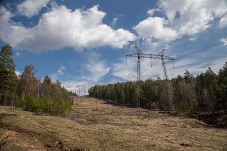 Mountain slope with power line. Clearing in the forest. Beautiful nature on a sunny day. Blue sky with clouds.