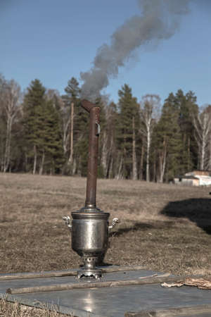 An old samovar heats water outdoors in the village. Smoke from the chimney. Sunny day. Rural nature.