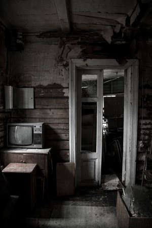 An old gloomy room in an abandoned house. Antique TV. Broken door. Wooden ragged dirty walls.