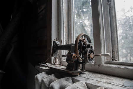 Antique rusty sewing machine on a windowsill in an abandoned house. Old technique. Wooden walls. Dirty window.
