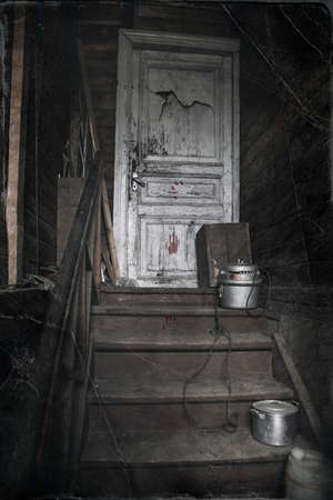 Old wooden staircase in an old abandoned house. White door. Wooden ragged walls. Gloomy atmosphere. Stock Photo