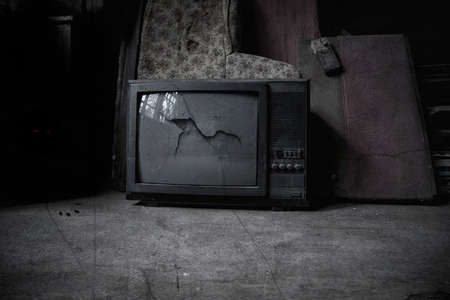 Old TV in the room of an abandoned house. Shabby walls and floor. The dark atmosphere of an abandoned building.