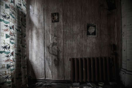 Scary old room in an abandoned house. Old magazine pages hang on the wall. Shabby walls. Gloomy atmosphere. Translation of the inscription on the wall - Crocodile Magazine 1979.