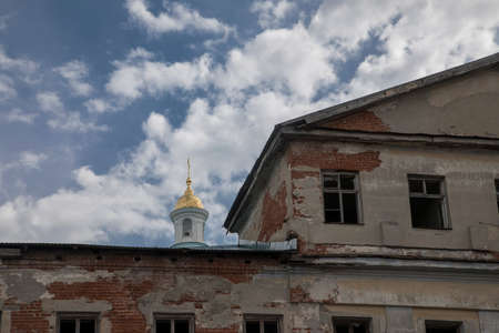 The beautiful dome of the church rises behind an abandoned building. An old abandoned house. Blue sky.