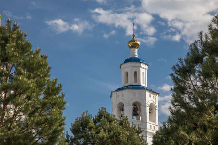 A beautiful white tower with a dome among the trees. An old church. Sunny day. Harmony with nature
