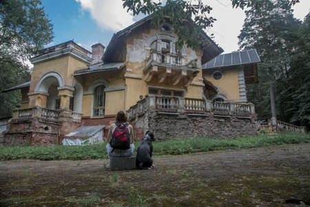 The girl and the dog sit with their backs and look at the old abandoned manor. Ancient architecture. Girl with a backpack. Black and white dog.
