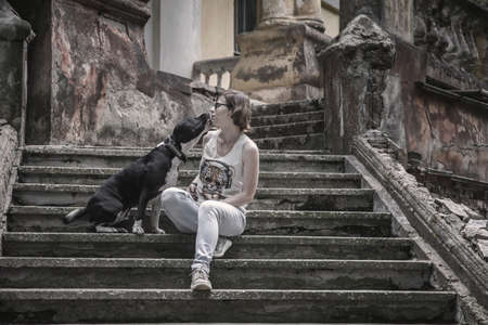 A girl and a dog are sitting on a stone staircase. An old abandoned manor. Black and white dog. Beautiful girl. Old architecture.