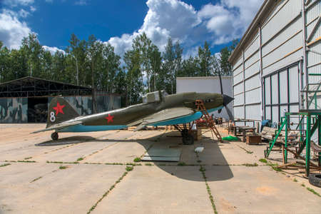 An old abandoned military plane stands in the open air. Old abandoned machinery. Red stars on the tail. A sunny day.