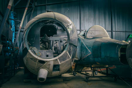 The remains of old abandoned aircraft lie in the hangar. Old abandoned machinery. Stock Photo