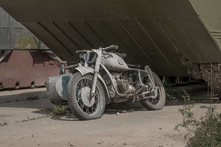 An old abandoned motorcycle with a sidecar. Abandoned motor vehicles. Sunny day. Stock Photo