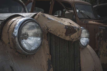 Headlights and old front of an abandoned car. Old rusty car. A beautiful element of an abandoned car.