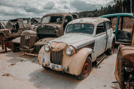 Old rusty car in the abandoned car graveyard. Old shabby rusty car. Car graveyard.