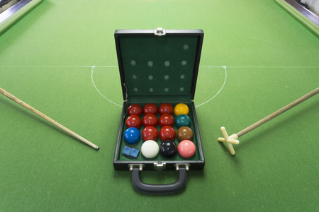 snooker cue: A box of snooker balls on the snooker table with chalk, rest and cue. Stock Photo