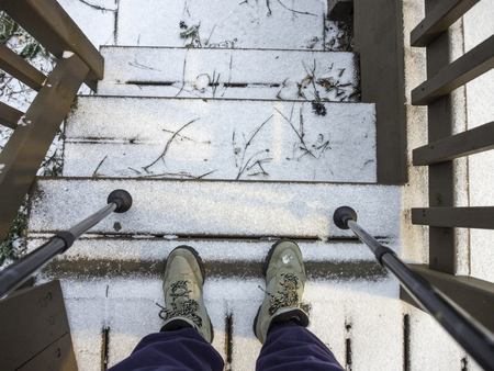 pantalones abajo: botas y palos de caminante en las escaleras con la nieve