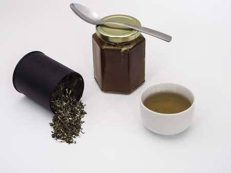 Dried herbs make up the tulse with a jar of chestnut honey with spoon on cover and cup of tea