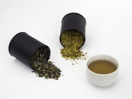 lemongrass tea: Two canisters of herbs spilling onto background with a cup of tea