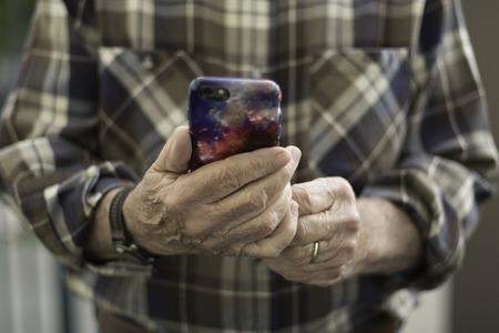 ブラウンの格子縞のシャツを保持しているモバイル デバイス顔の男 写真素材 - 72083720