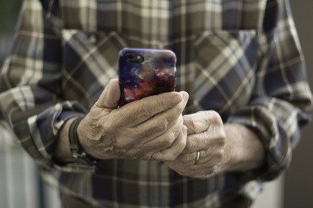 Man in Brown Plaid Shirt Holding mobile device face on